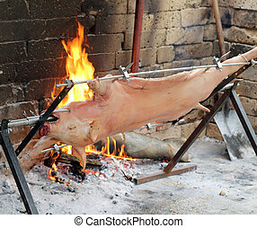 cooked whole pig on a spit with hot embers