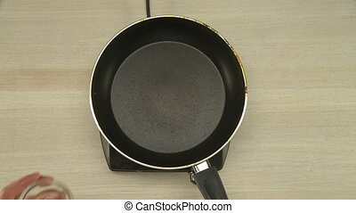 Cooker putting vegetable oil on hot frying pan that stands ...