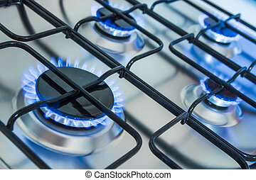 Cooker with blue gas flames - Cooker turned on in a kitchen...