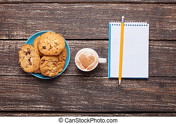 Cookie and cup with coffee, pencil and notebook.