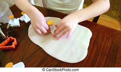 A girl is making a shaped cookie on a table