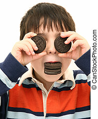 Adorable five year old boy playing with cookies.