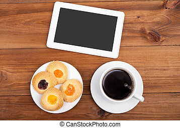 Cookies and coffee cup digital tablet computer on a wooden table.
