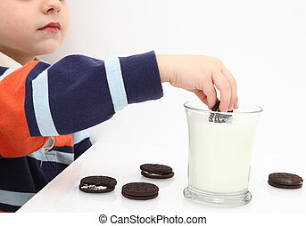 Cookies and Milk - Small boy dunking cookies in milk.