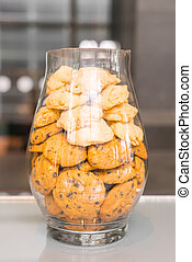 Cookies in a glass jar on table .