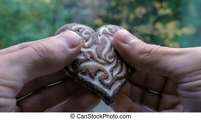 cookies in the shape of a heart broken in the hands. slow-motion
