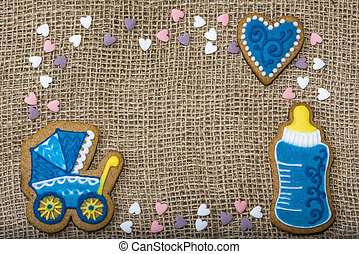 Cookies on a burlap in the form of a stroller in a bottle of baby hearts.
