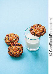 Cookies with a glass of milk on a light blue background.