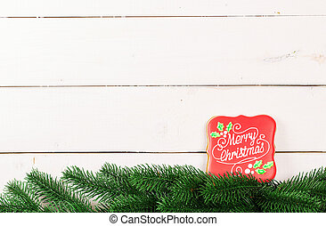 Cookies with branches Christmas tree. Gingerbreads with wishes for a Merry Christmas on white wooden background. Free space for your text.