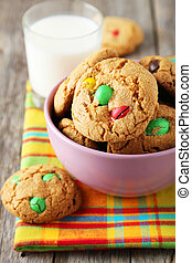 Cookies with colorful candy in bowl on grey wooden background