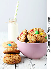 Cookies with colorful candy in bowl on white wooden background