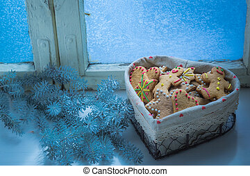 Cookies with frozen window for Christmas in cold evening