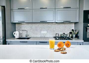 Cookies with glass of orange juice on the kitchen table, blurred background.