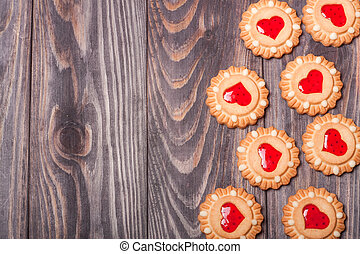 cookies with jelly on a dark wooden background