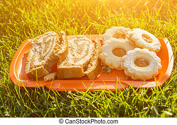 Cookies with marmalade on the grass in a sunny day