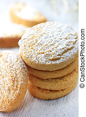 Cookies with powdered sugar on white wooden board