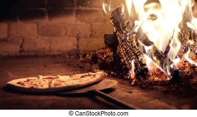 cooking a pizza in a wood fired ove