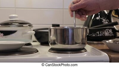 cooking a porridge stirring with a spoon.