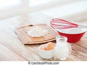 jugful of milk, eggs in a bowl and flour