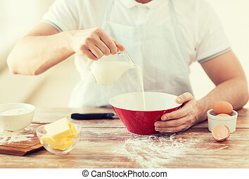 close up of male hand pouring milk in bowl - cooking and ...