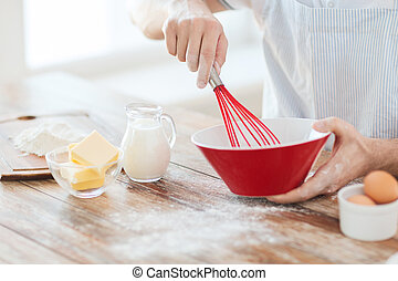 close up of male hand whisking something in a bowl - cooking...
