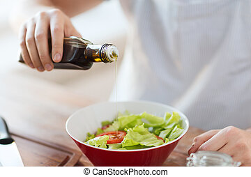 close up of male hands flavouring salad in a bowl - cooking ...