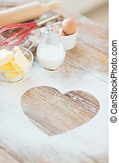 close up of heart of flour on wooden table at home