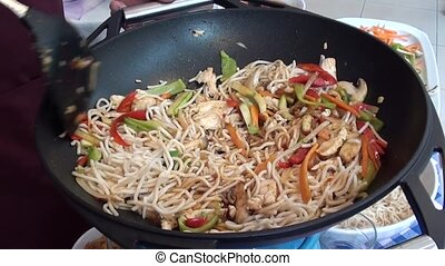 Cooking and stirring Chinese pasta with vegetables