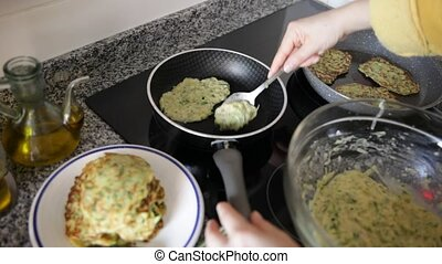 Tasty fritters of courgettes are fried in pan. Healthy vegetarian homemade snack