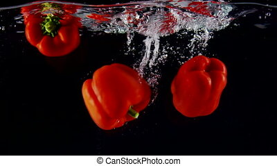 Cooking background red bell peppers falls into water with splashes on black