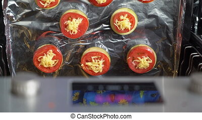 Cooking baked eggplant topped with cheese and tomato in the oven