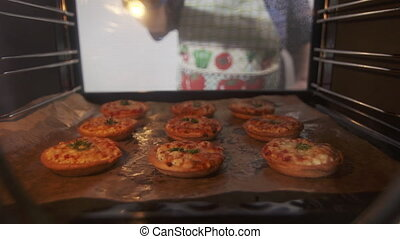 Woman takes out cooked crispy crust small pizzas from the...