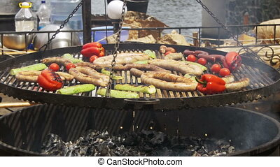 Cooking Barbecue Delicious Sausages and Vegetables on the Grill