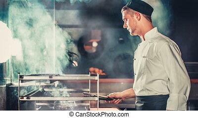 Cooking beef steak in the kitchen modern interior - Chef in...