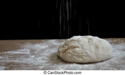 Raw bread is prepared for baking on a black background on the table. The bread is sprinkled with flour to make it crispy. This video was taken close-up with natural light in 4k