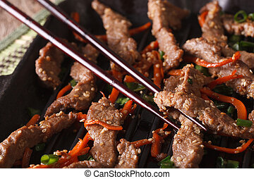 Cooking Bulgogi beef with carrot on the grill macro....