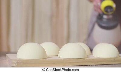 Cooking cakes with white velour coating. Close up hands of...