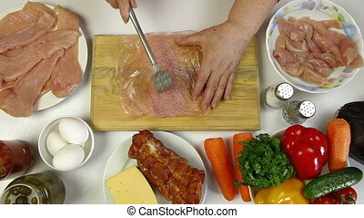 Women's hands cooking chicken breast. Tenderizing, salt, pepper. Top view