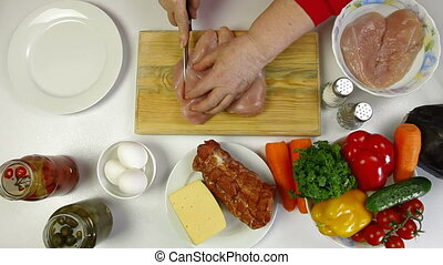 Women's hands cutting chicken breast. Shoot from above