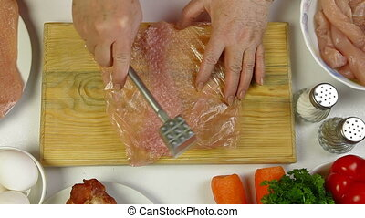 Cooking Chicken Breast - Women's hands tenderizing chicken...