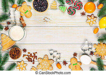 Cooking Christmas gingerbread cookies with the ingredients, dough, candy and winter spices decorating for new year celebration on white wooden table. Xmas food frame background