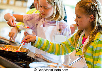 Kids learning how to cook in a cooking class.