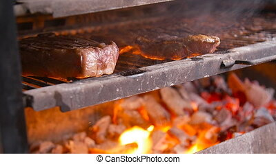 Cooking concept. Two grilling steaks on flaming grill with...