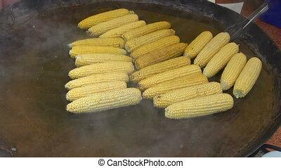 cooking corn cobs on big metal pot