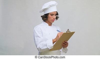 female chef in toque with pen writing to clipboard - cooking...