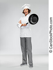 smiling female chef in toque with frying pan