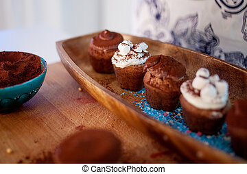 cooking cupcakes, muffins and a plate of ingredients for decoration on the table