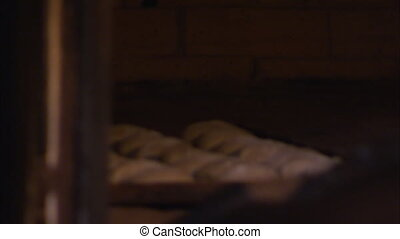 Cooking dough in an oven - A tracking shot of a dough as a...