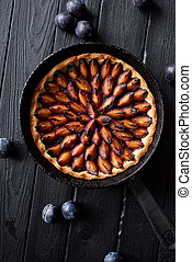 Cooking failure. Burned plum pie in cast iron pan on black background top view. Low key still life with natural lighting