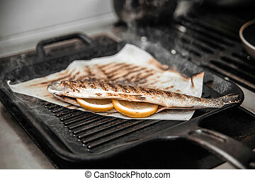 Cooking fish on a grill with lemon